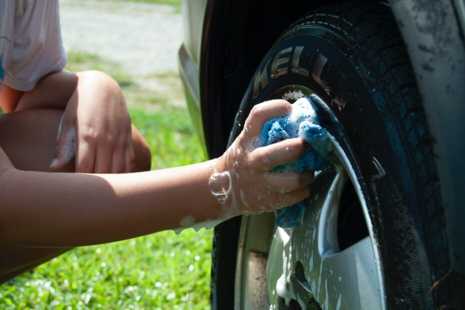 person washing vehicle tire
